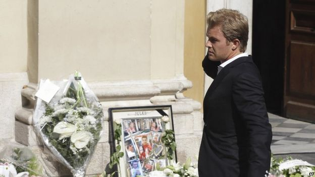 Mercedes driver Nico Rosberg of Germany stands next to floral tributes outside the cathedral